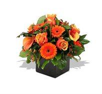 סידור כתום בכלי מיוחד השזור ממגוון פרחים שמאירים את החדר