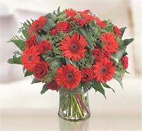 RED, זר בגוונים של אדום המורכב מוורדים אדומים וגרברות אדומות