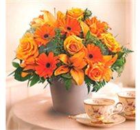 סידור ליליות כתום מרהיב השזור ממגוון פרחים שמאירים את החדר